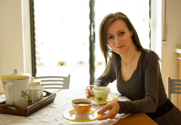 Portrait Of Smiling Woman Giving Tea At Home