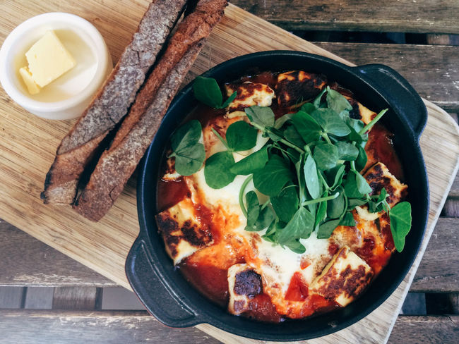 Spicy middle eastern baked eggs with bread on a wooden platter Baked Baked Eggs Board Breakfast Brunch Egg Food Middle East Style Middle Eastern Flavours Overhead Tomatoes