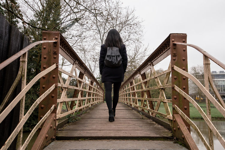 A young woman with black hair and dressed in black alone walks across a steel footbridge crossing a small river. Cambridge Cambridgeshire University City Backpack Behind Black Backpack Black Clothes Black Hair Black Tights Bridge Dark Clothes Foot Bridge From Behind Leather Backpack Metal Bridge Rear River Crossing Rivets Steel Bridge Walking Walking Away Woman One Person Railing Architecture Lifestyles Full Length Real People Casual Clothing Leisure Activity Tree Wood - Material Young Women The Way Forward Built Structure Rear View Young Adult Staircase Footbridge Direction Bridge - Man Made Structure Steps And Staircases Outdoors Warm Clothing