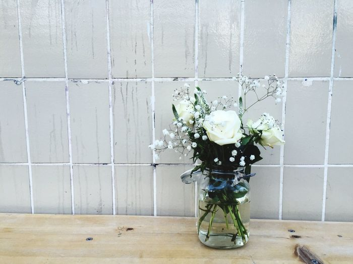 White flowers in vase on table by wall