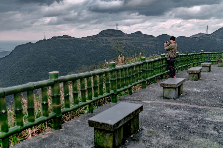 Man standing on railing against mountains