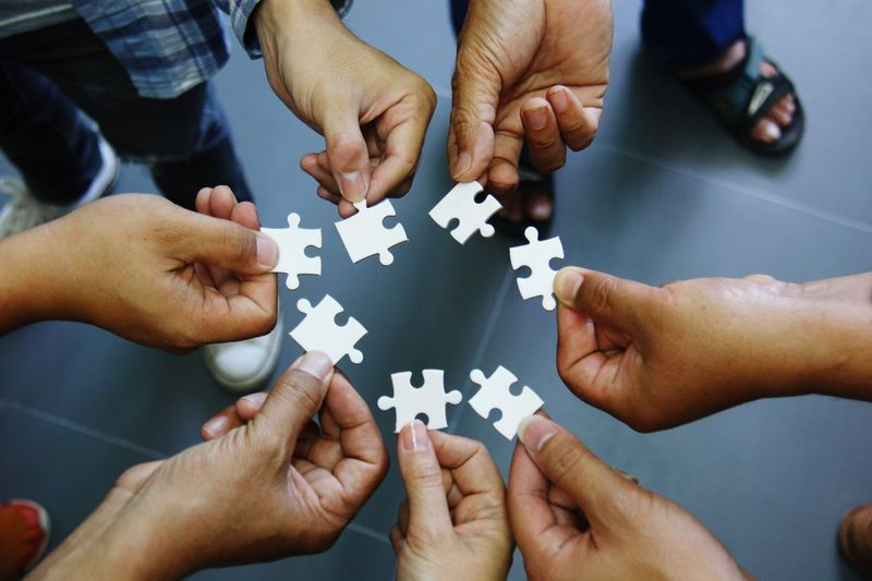 High angle view of people holding puzzles