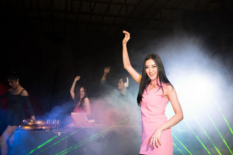Portrait of happy young woman dancing against friends and dj in nightclub