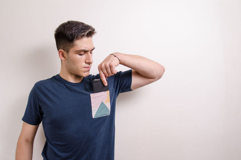 Young man looking away against white background