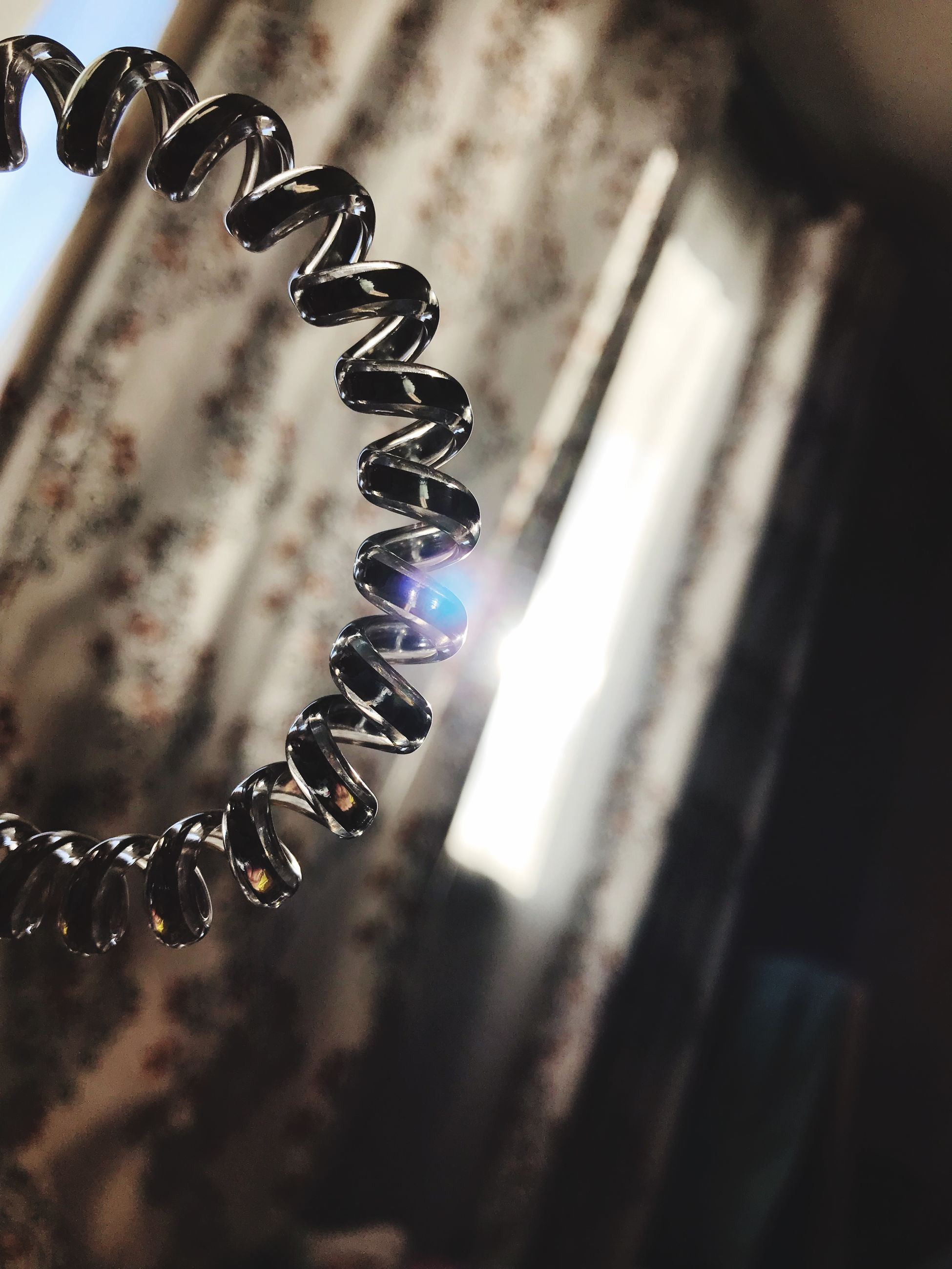 no people, close-up, metal, selective focus, indoors, focus on foreground, wood - material, jewelry, still life, nature, old, spiral, sunlight, day, in a row, illuminated, corkscrew, chain, personal accessory, ornate