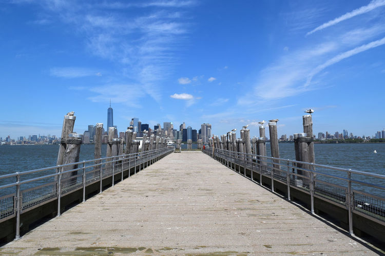 Seagulls perching on wooden columns by empty pier at hudson river against sky