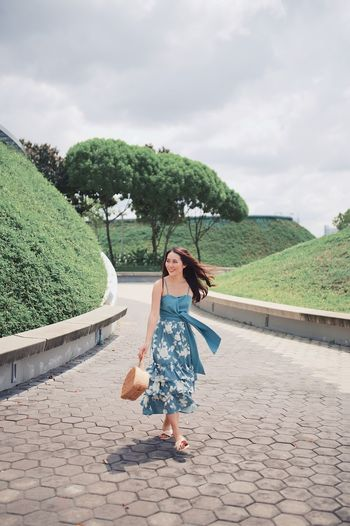 Smiling woman holding bag while walking on footpath