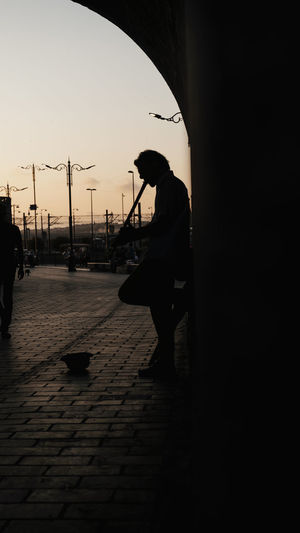 Real People One Person Silhouette Lifestyles Sky Full Length Architecture Adult Men Sunset Leisure Activity Footpath Transportation Women City Street Walking Built Structure Nature Outdoors Flute The Street Photographer - 2019 EyeEm Awards The Great Outdoors - 2019 EyeEm Awards
