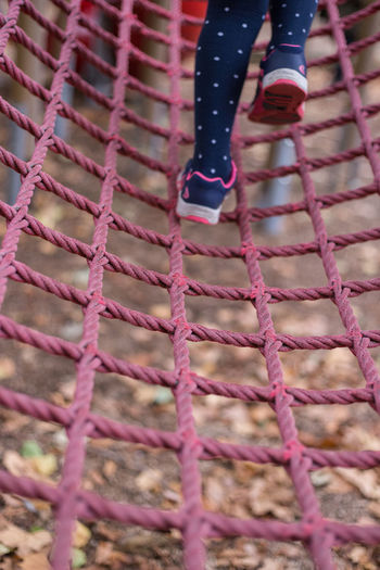 Pink Rope Apparatus Child Childhood Climbing Climbing Frame Equipment Frame Human Body Part Human Leg Leisure Activity Low Section One Person Outdoors Pattern Pink Color Play Equipment Playground Real People Strength Strong Perspectives On People Mobility In Mega Cities