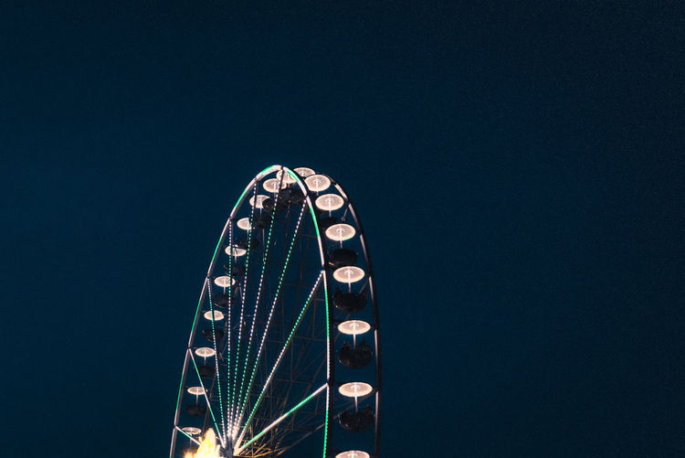 Low angle view of illuminated ferris wheel against blue sky at nicht