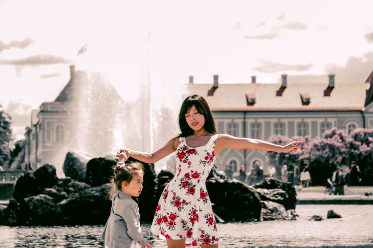 Woman Dancing With Daughter Against Fountain