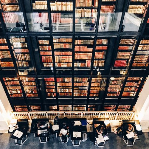 Directly above shot of people reading books against bookshelf at british library