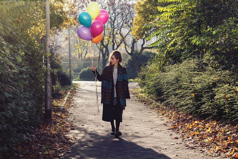 Full Length Of Young Woman Walking With Balloons At Park