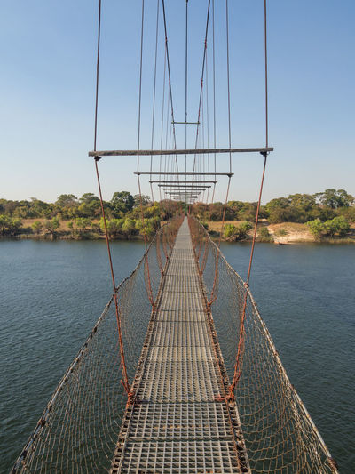 Footbridge over river zambezi against clear sky, chinyingi, zambia