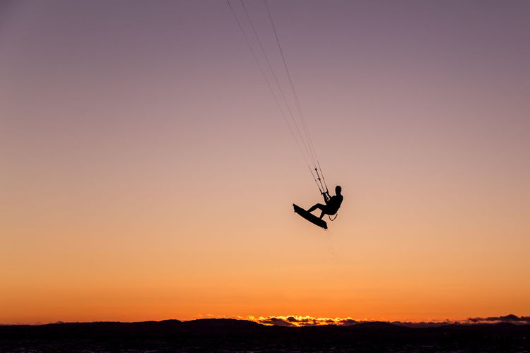 Silhouette person wakeboarding against sky during sunset