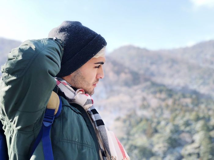 Man looking away against mountains during winter