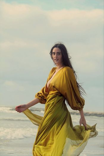 Young woman in yellow dress standing against  sky