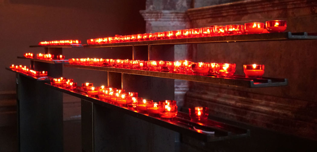 prayer candles Candles Church In A Row Red Burning Candle Flame Illuminated Lit Many No People Prayer Prayer Candles Religion Row Spirituality