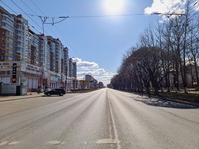 Cars on road in city against sky