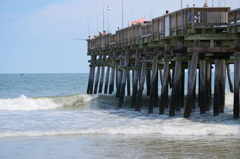 People fishing on pier over sea