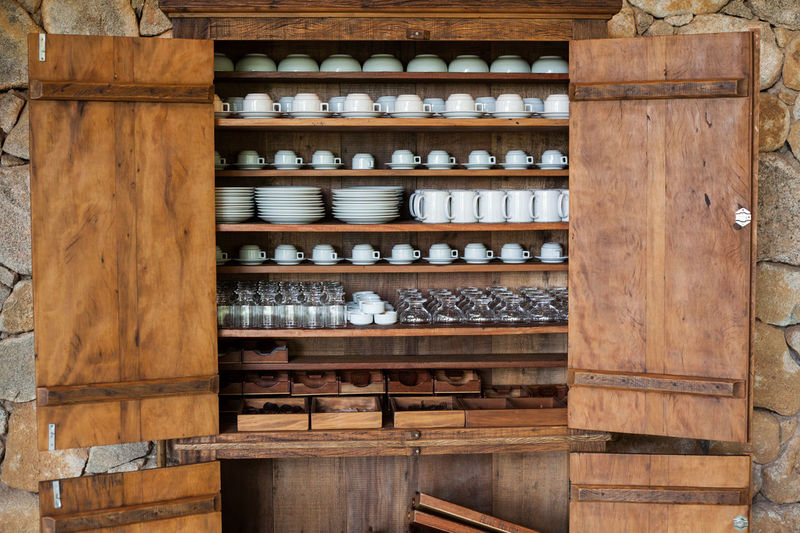 Various Crockery Arranged On Wooden Cabinet At Kitchen