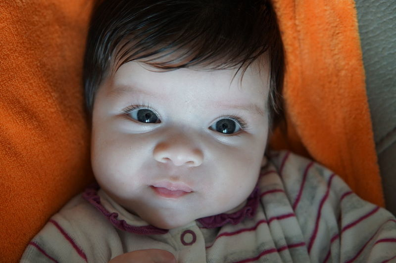 Portrait Of Cute Baby Girl Lying On Bed