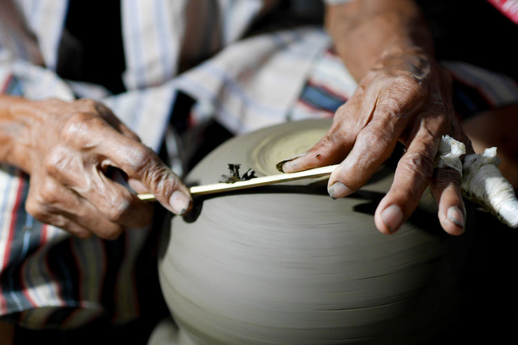 Cropped hands making pottery in workshop