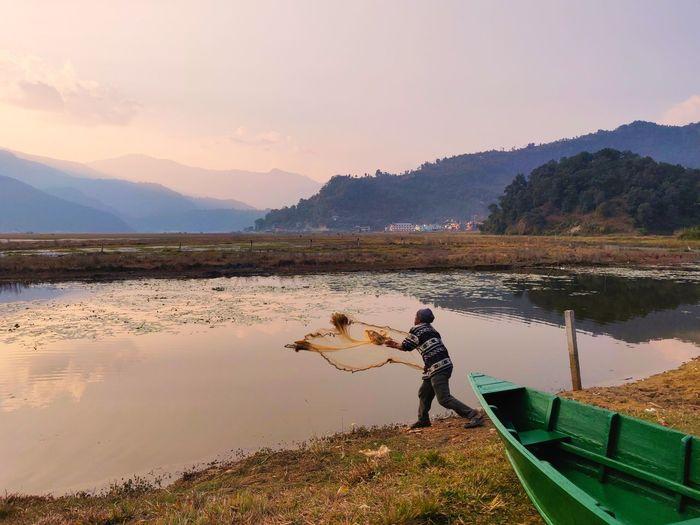 Side view of man throwing fishing net in lake
