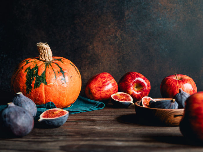 Close-up of pumpkin and fruits on table