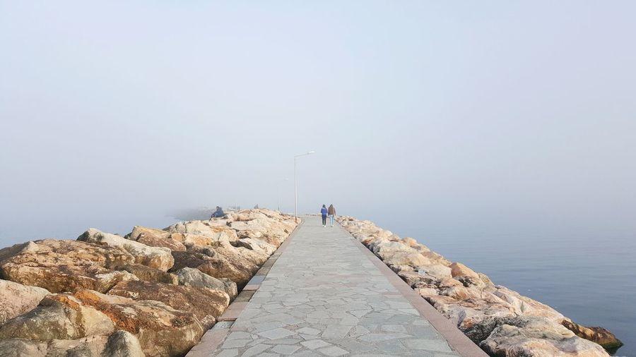 Rear view of friends on walkway in foggy weather