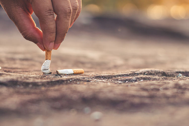Men hand caught a burning cigarette causing smoke, concept stop smoking.
