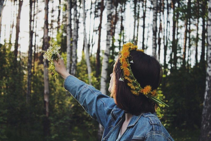 Side view of woman wearing flowers against trees at forest