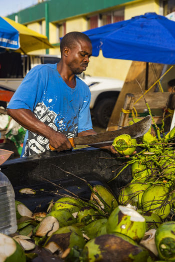 Man opening Coconuts with a Machete Castries Central Market, Castries, Saint Lucia Adult Day Food Freshness Market Market Stall Market Vendor Men Occupation One Man Only One Person Outdoors People Real People Working Young Adult