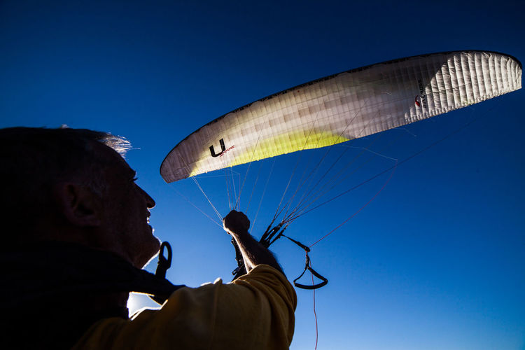 Low angle view of man flying against clear blue sky