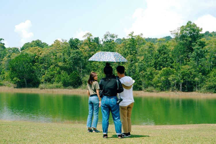 Rear view of people by lake against trees