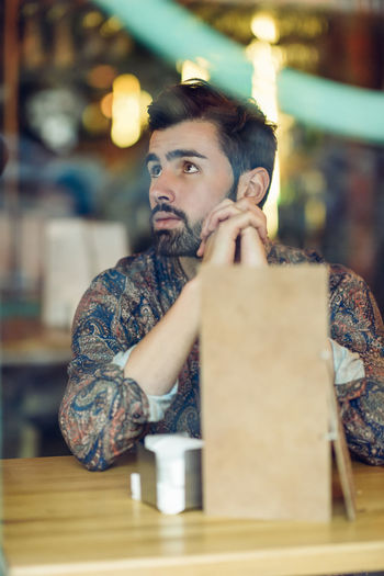 Thoughtful Man Sitting At Table In Restaurant