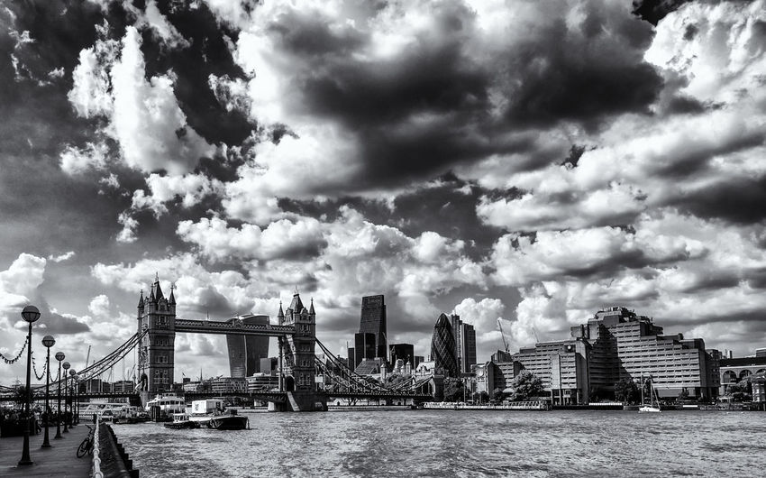 Tower bridge and cityscape against cloudy sky