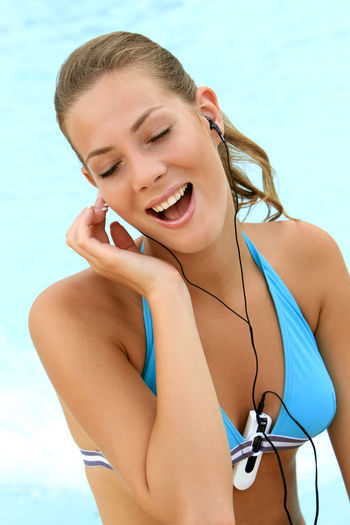 young blond woman listening to music with MP3 players at the pool Beautiful Happy Holiday Listening Music Music Summer Holidays Woman Beautiful Woman Bikini Blond Girl Happyness Leisure Leisure Activity Lifestyles Mp3 Player One Person Pretty Relaxation Swimming Pool Swimwear Vacation Water Wellbeing Young Adult