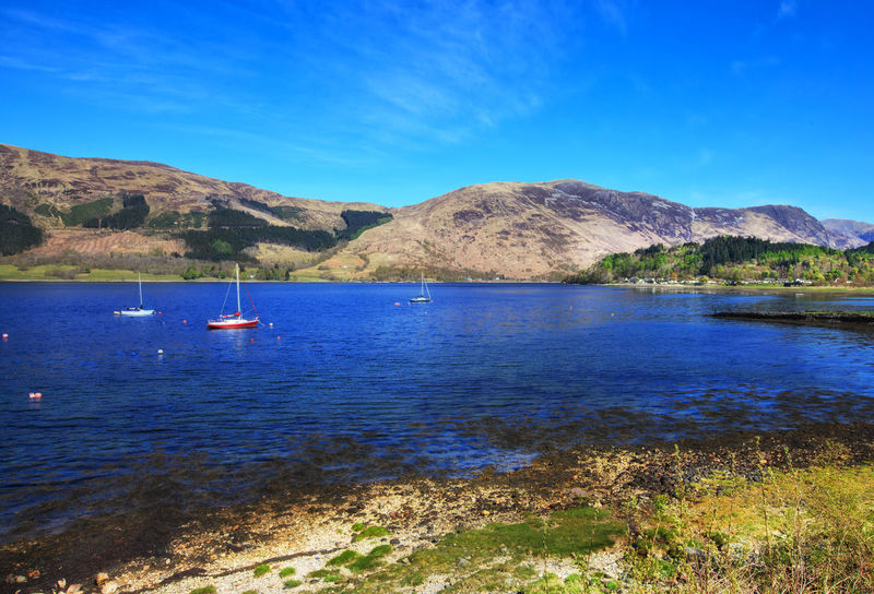 Loch Leven, Scottish Highlands, Scotland, UK Beauty In Nature Blue Cliff Coastline Day Lake Landscape Loch Leven Mountain Mountains Nature Nautical Vessel No People Outdoors Sailboat Scenics Scotland Scottish Highlands Sea Sky Tranquil Scene Tranquility Travel Destinations Uk Water