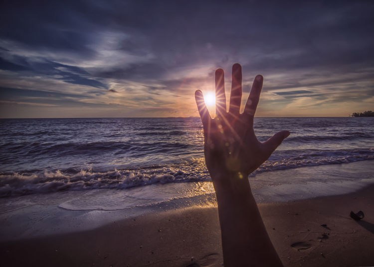 Cropped Hand Against Sea During Sunset