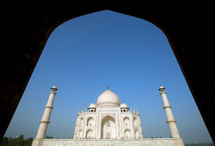 Low angle view of taj mahal seen through arch against clear sky