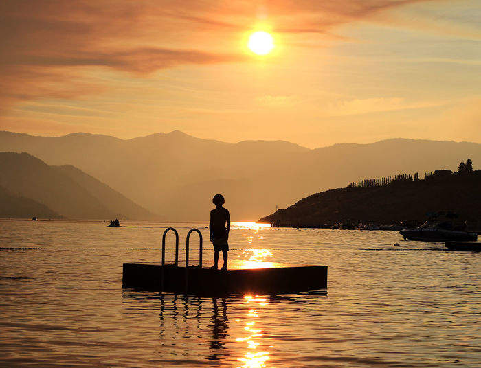 Silhouette boy standing on floating platform in lake