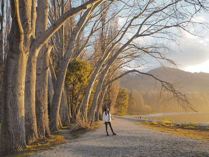Woman Standing By Bare Trees