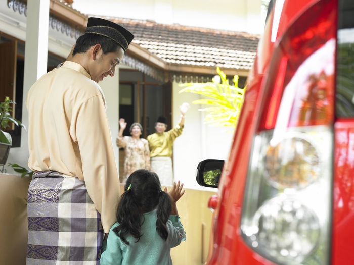 man brought child visit grandfarther during raya festive Asian  Family Festival Season Going Home Grand Parents Hari Raya Aidilfitri Relationship Selamat Hari Raya Transportation Arm Raised Baju Raya Balik Kampung Car Childhood Day Festival Home Town Islamic Event Lifestyles People Real People Rear View Son Standing Waiving