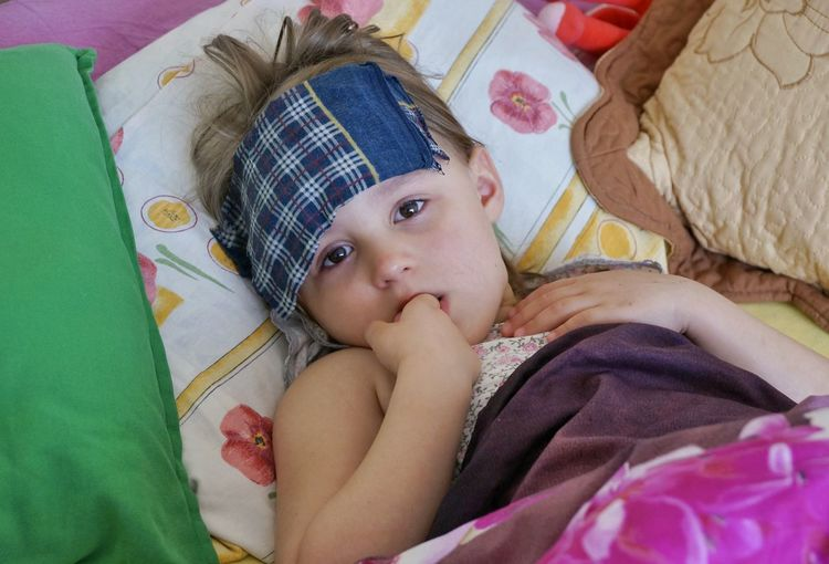Portrait of cute girl with fever lying on bed