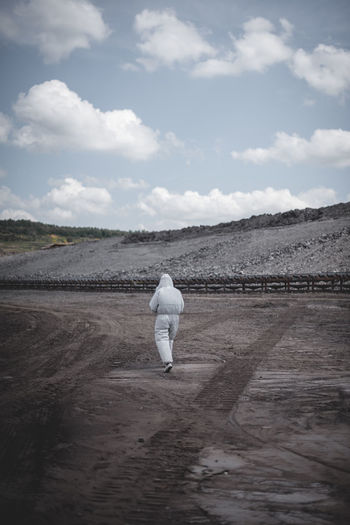 Rear view of worker in protective clothing walking on field at mining industry against sky