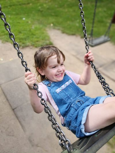 Smiling Cute Girl Swinging In Playground
