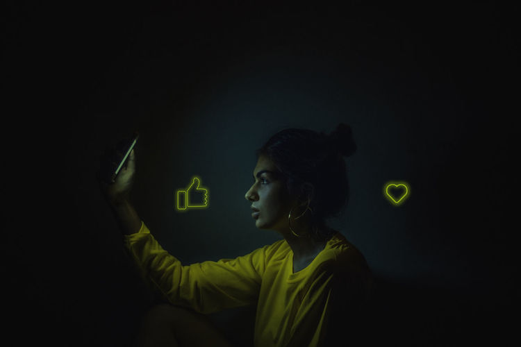 Profile view of woman using phone with icons in darkroom