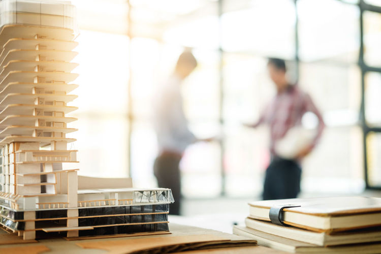 Close-up of building model on desk with business colleagues discussing in background