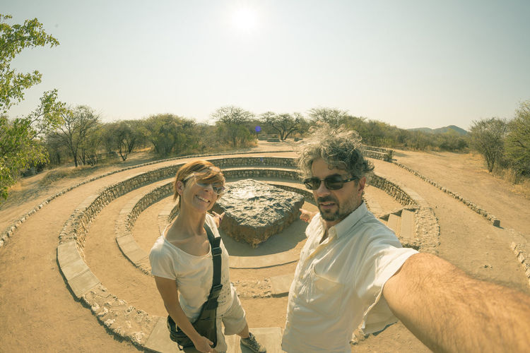 Couple taking selfie while standing at hoba meteorite